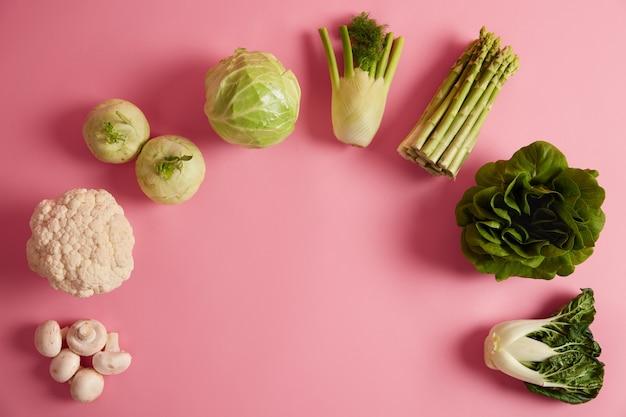 Postura plana de vegetais de folhas verdes maduras contendo muitas vitaminas e nutrientes. cogumelos, brócolis, erva-doce, aspargos, bok choy dispostos em semicírculo. alimentação orgânica, conceito de dieta saudável.