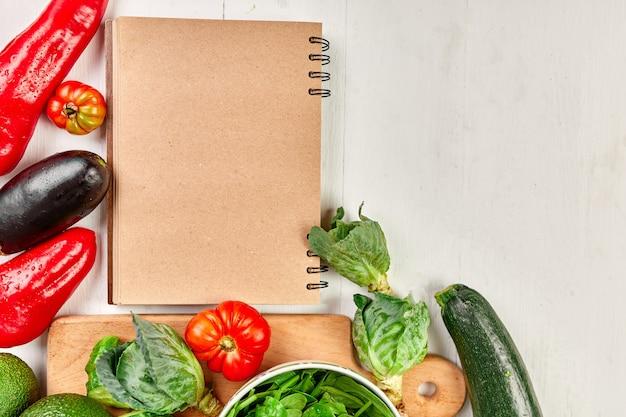 Postura plana de vegetais variados ao redor do livro de receitas culinárias