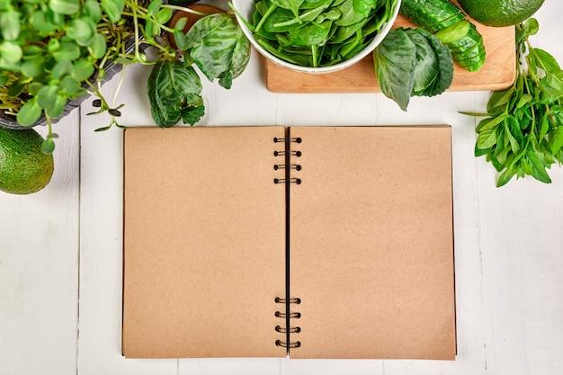 Postura plana de vegetais verdes variados ao redor do livro de receitas culinárias