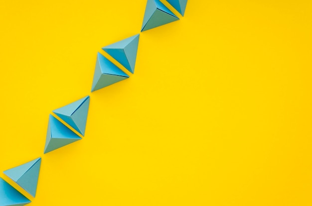 Postura plana de vibrante linha de pirâmides de papel com espaço de cópia