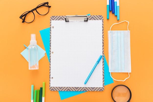 Postura plana de volta ao material escolar com bloco de notas e máscara médica