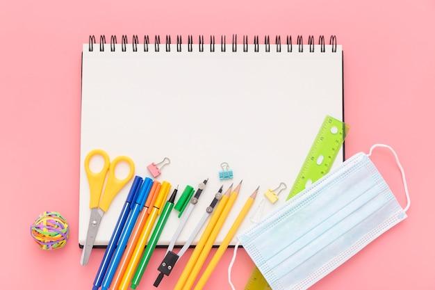 Postura plana de volta ao material escolar com caderno e lápis
