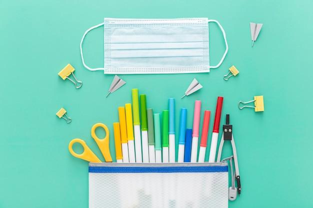 Postura plana de volta ao material escolar com lápis e máscara facial