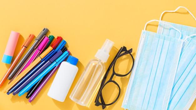 Postura plana de volta ao material escolar com lápis e máscaras