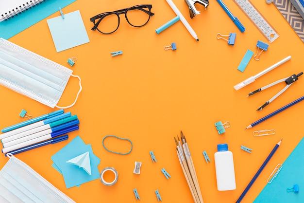 Postura plana de volta ao material escolar com óculos e desinfetante para as mãos
