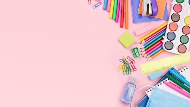 Postura plana de volta aos artigos de papelaria da escola com lápis coloridos e espaço de cópia