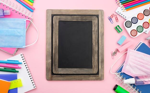 Postura plana de volta aos artigos de papelaria da escola com quadro-negro e lápis coloridos