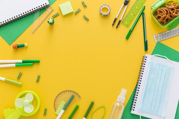 Postura plana de volta aos materiais escolares com caderno e máscara facial