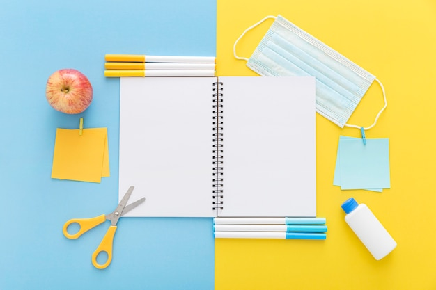 Postura plana de volta aos materiais escolares com notebook e apple