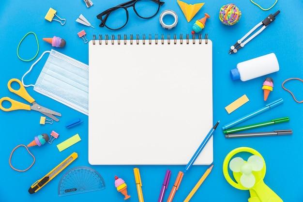Postura plana de volta para materiais escolares com caderno e tesoura