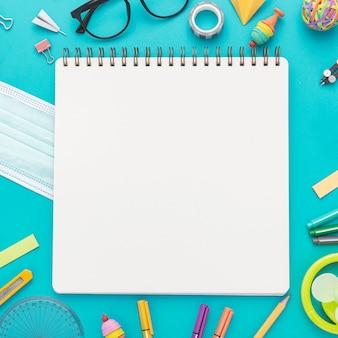 Postura plana de volta para materiais escolares com lápis e caderno