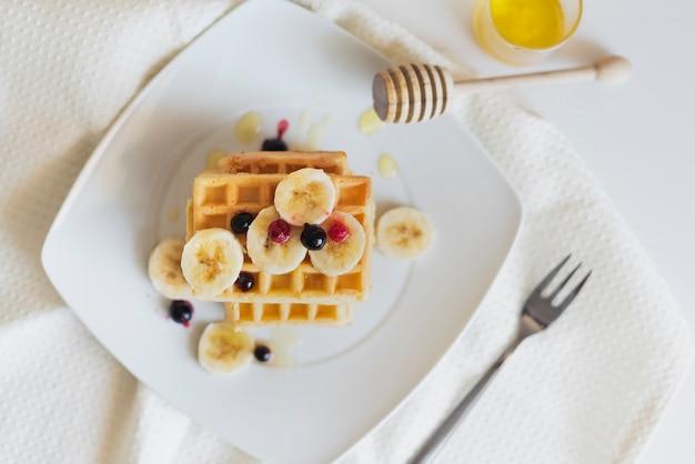 Postura plana de waffers com frutas e mel