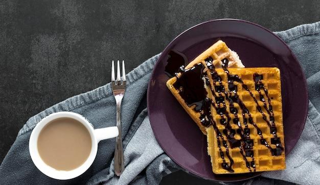 Postura plana de waffles cobertos de chocolate no prato com garfo e café