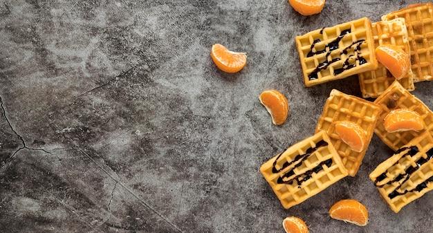 Postura plana de waffles com calda de chocolate e tangerinas