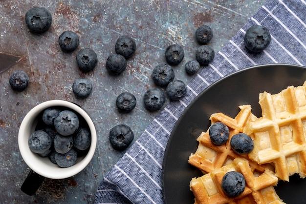 Postura plana de waffles e mirtilos no prato