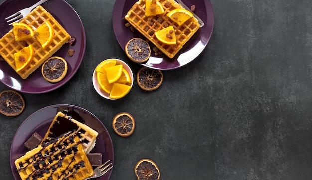 Postura plana de waffles em pratos com chocolate e frutas cítricas