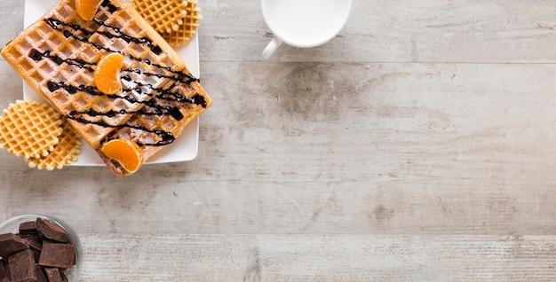 Postura plana de waffles no prato com leite e chocolate