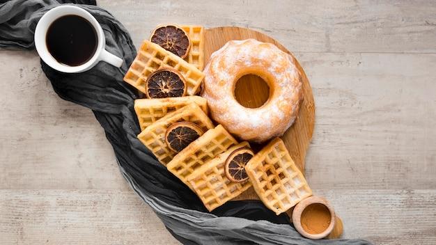 Postura plana de waffles no prato com rosquinha e frutas cítricas secas