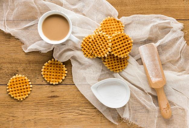 Postura plana de waffles redondos com café e colher de madeira