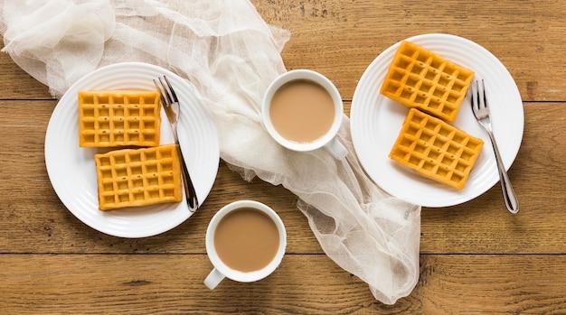 Postura plana de waffles simples em pratos com café e garfos