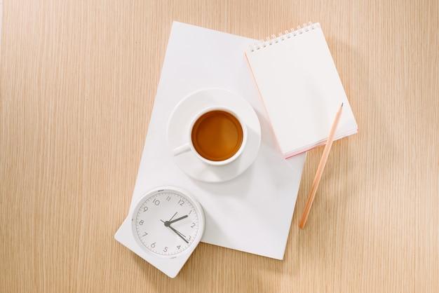 Postura plana de xícara de café, relógio, lápis e um caderno.