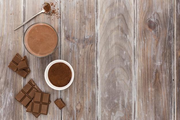Postura plana de xícara de chocolate quente com cacau em pó