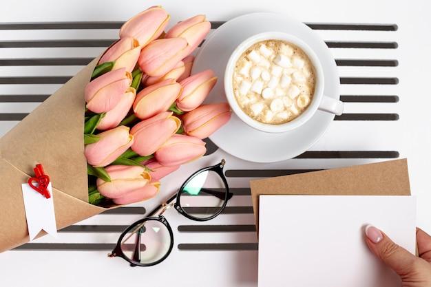 Postura plana de xícara de marshmallows com tulipas e óculos