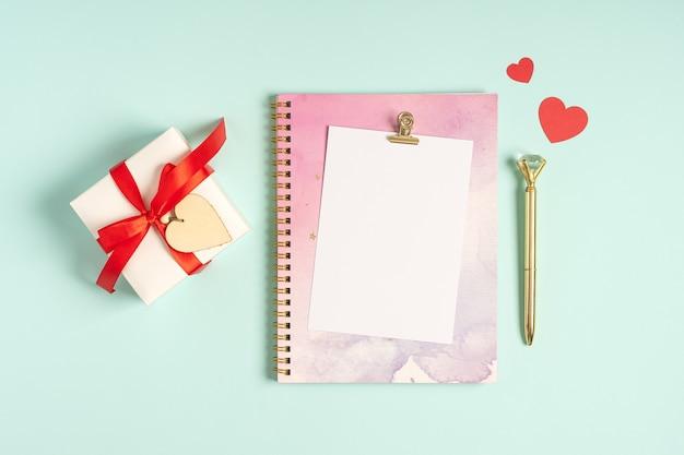Postura plana do bloco de notas de carta em branco com presente de dia dos namorados.