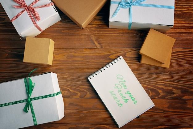 Postura plana do bloco de notas de motivação e caixas de presente no fundo da mesa de madeira, ano novo, começar, christma ...