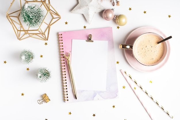 Postura plana do bloco de notas em branco com uma xícara de café e decoração de natal.