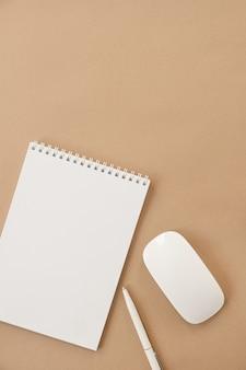 Postura plana do caderno espiral de folha em branco em bege pastel. espaço de trabalho minimalista da mesa do escritório em casa. negócio, modelo de trabalho. camada plana, vista superior