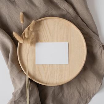 Postura plana do cartão de visita de papel em branco com cauda de coelho em bandeja de madeira em cobertor bege neutro