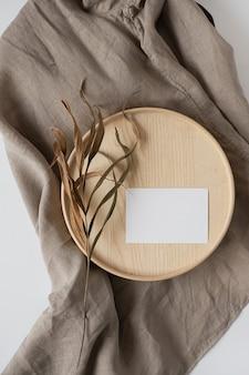 Postura plana do cartão de visita de papel em branco com flores na bandeja de madeira em um cobertor bege neutro