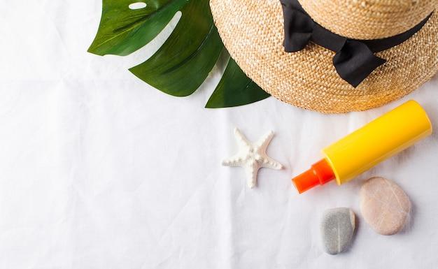 Postura plana do chapéu, protetor solar de conchas do mar na toalha branca com espaço de cópia