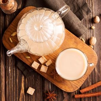 Postura plana do conceito de chá de leite na mesa de madeira