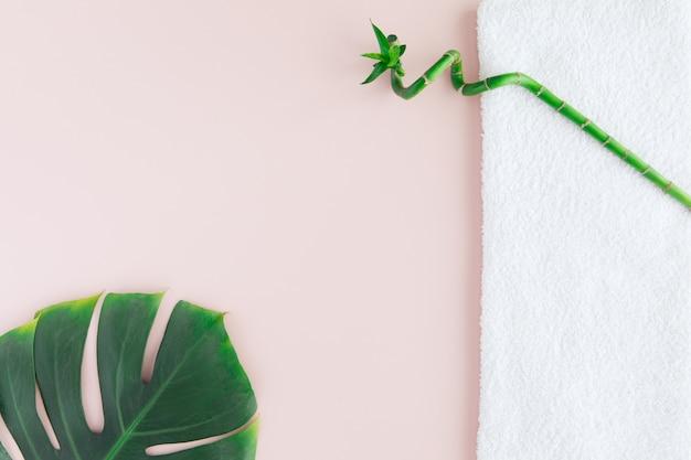 Postura plana do conceito de spa com toalha branca, bambu e folha de palmeira, spa com um espaço para um texto, flatlay