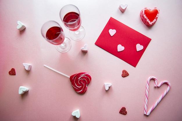 Postura plana do dia dos namorados com duas taças de vinho, coração vermelho, doces e envelope de carta de amor no fundo rosa