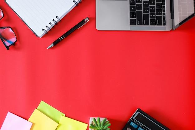 Postura plana do espaço de trabalho do escritório com laptop, livro, suculenta e acessórios isolados em fundo vermelho
