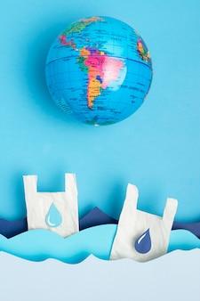 Postura plana do globo da terra com ondas do mar de papel e sacos de plástico