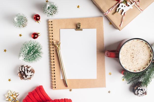 Postura plana do planejador de área de trabalho em branco com xícara de café e decoração de natal
