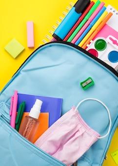 Postura plana dos itens essenciais da escola com mochila e desinfetante para as mãos