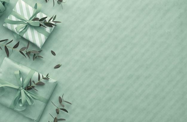 Postura plana em tons de verde claro com caixas de presente embrulhadas, decoradas com galhos de eucalipto, cópia-espaço