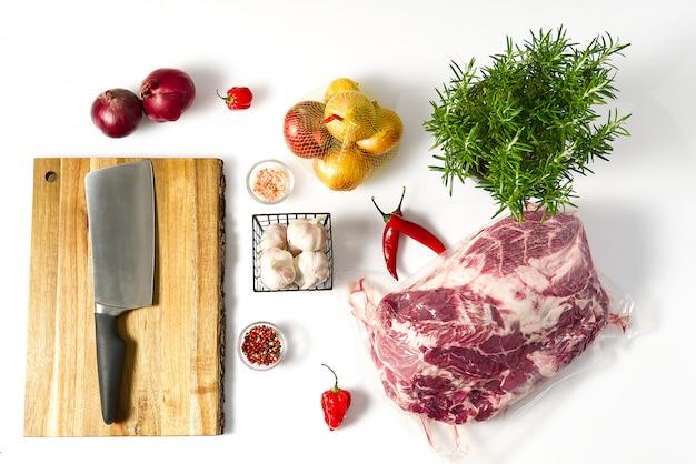 Postura plana na cozinha doméstica, cozinhando o conceito na mesa branca. carne de porco crua, cebola, alecrim, alho, tábua, pimenta.
