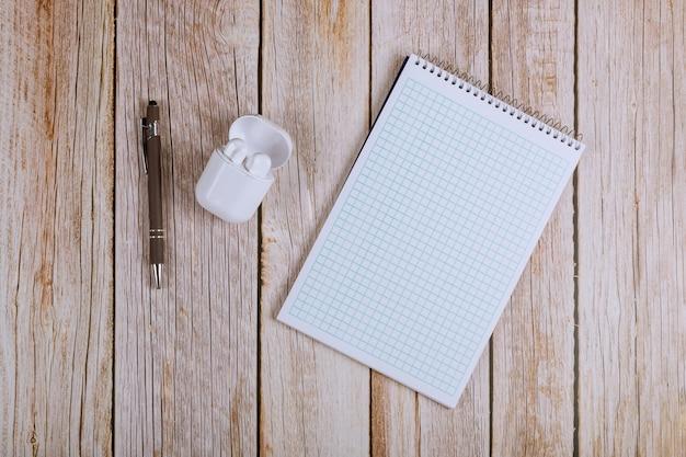 Postura plana na mesa de escritório de espaço de trabalho com notebooks, fones de ouvido sem fio e caneta