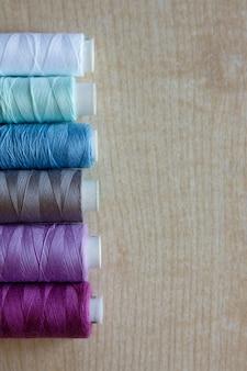 Postura plana. novelos de fios de cores diferentes repousam sobre uma mesa de madeira clara