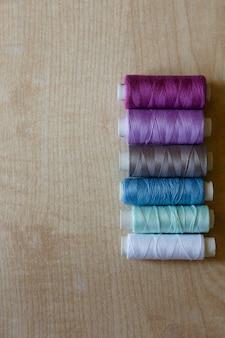 Postura plana. novelos de fios de diferentes cores repousam sobre uma mesa de madeira clara