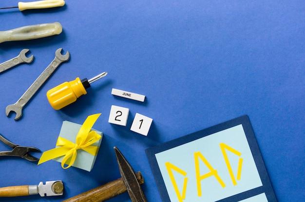 Postura plana para o dia dos pais com ferramentas e caixa de presente em um fundo azul