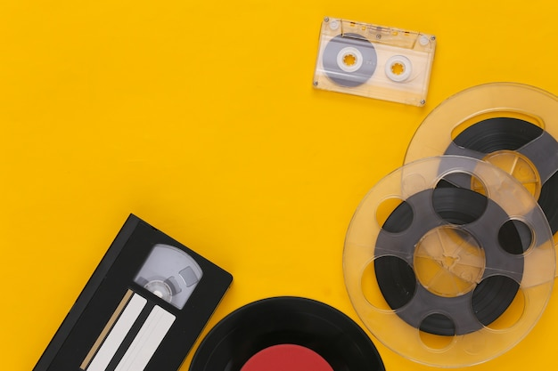 Postura plana retro. carretel de fita magnética de áudio, cassete de áudio e vídeo, placa de vinil em amarelo