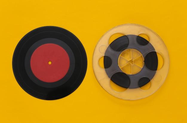 Postura plana retro. carretel de fita magnética de áudio e placa de vinil em amarelo
