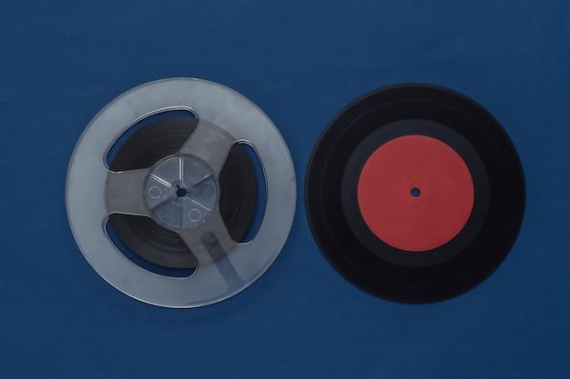 Postura plana retro. carretel de fita magnética de áudio e placa de vinil em azul clássico